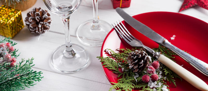 Romantic red Christmas table setting with red plates, with red Christmas ornaments and spruce branches on a wooden white background