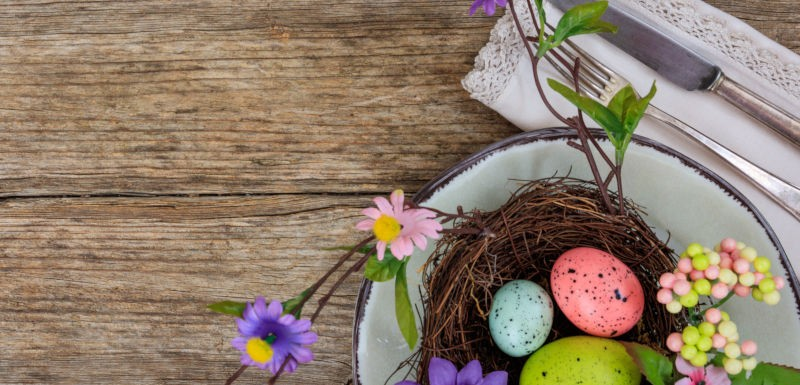 Easter eggs on a plate on wooden background with copy space